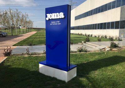 Tótem Joma instalado sobre pedestal de piedra, en instalaciones de Joma