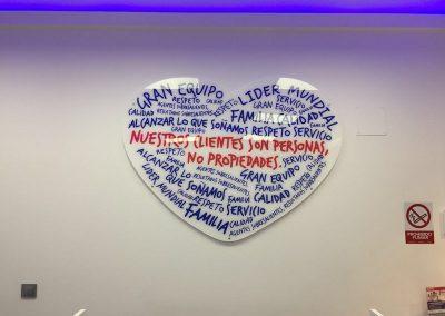 Placa corporativa de metacrilato con forma de corazon decorado con vinilo de corte