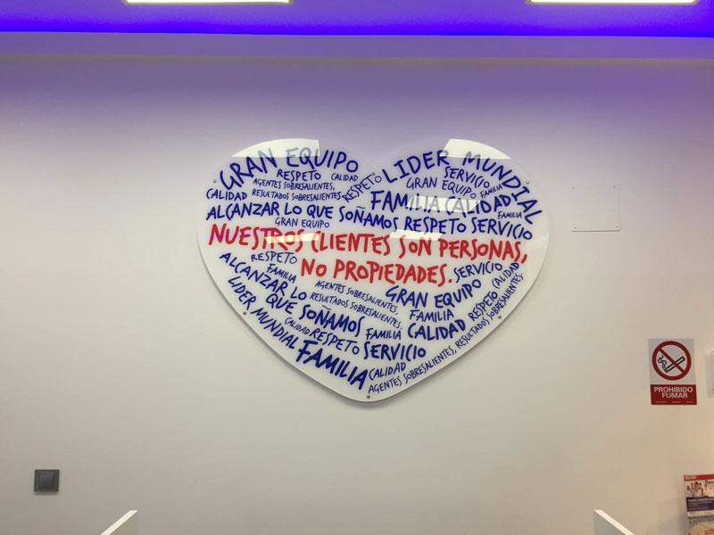 Placa corporativa de metacrilato con forma de corazon decorado con vinilo de corte Placas corporativas